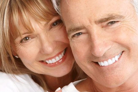 Couple showing off their dental impants and dentures.